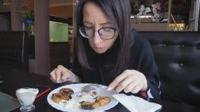 La muchacha hermosa cena en el restaurante, comiendo el plato caliente servido delicioso cenando muy bien metrajes