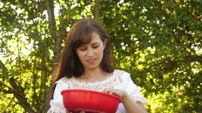 La muchacha hermosa come la fresa roja de una taza y de sonrisas Dieta de la vitamina y de la baya para las mujeres consumición f almacen de video