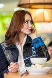 La muchacha hermosa come la 'fondue' de chocolate Fotos de archivo libres de regalías