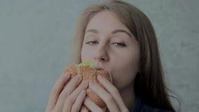 La muchacha hermosa come una hamburguesa Restaurante de los alimentos de preparaci?n r?pida almacen de metraje de vídeo