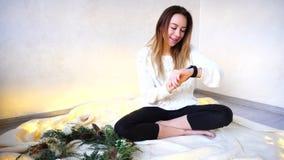 La muchacha hermosa comunica usando el reloj elegante moderno y prueba g Fotografía de archivo