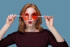 La muchacha hermosa con dos que el caramelo rojo redondo del caramelo se cierra los ojos, atornillando su cara retuerce los labio Imágenes de archivo libres de regalías