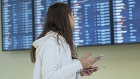 La muchacha hermosa con el pasaporte y el boleto en sus manos utiliza el teléfono y llega horario de la salida en tablero de la i metrajes