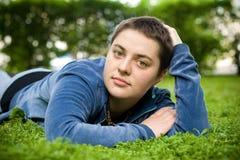 La muchacha hermosa con el pelo corto y los ojos verdes miente en la hierba y mira la cámara Fotografía de archivo