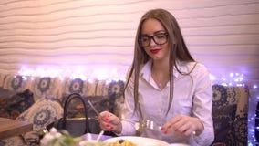 La muchacha hermosa con el pelo largo es desayunos en un café retrato de 4 k de la empresaria elegante joven hermosa que come ade metrajes