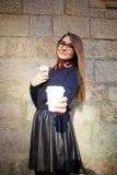 La muchacha hermosa con el pelo largo sostiene su café Fotos de archivo