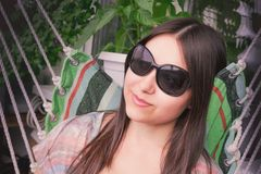 La muchacha hermosa con el pelo oscuro largo en gafas de sol est? descansando la sentada en una hamaca en el balc?n imagenes de archivo