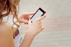 La muchacha hermosa con el pelo rizado que se coloca en la calle en teléfono a disposición, envía un mensaje de SMS lee foto de archivo