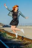 La muchacha hermosa con el pelo rojo salta en un día soleado, el modelo Fotos de archivo