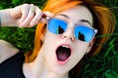 La muchacha hermosa con el pelo rojo y las gafas que llevan miente posición Fotos de archivo
