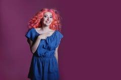 La muchacha hermosa con el pelo rosado en vestido azul muestra la muestra en el fondo de la lila, lugar para el texto Imagen de archivo
