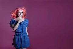 La muchacha hermosa con el pelo rosado en vestido azul muestra la muestra en el fondo de la lila, lugar para el texto Fotos de archivo