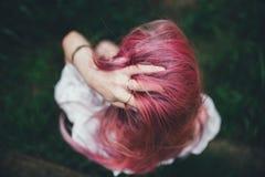 La muchacha hermosa con el pelo rosado se sienta en la escalera lanzada en un ambiente de una hierba verde Fotos de archivo libres de regalías