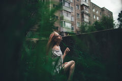 La muchacha hermosa con el pelo rosado se sienta en la escalera lanzada en un ambiente de una hierba verde Fotos de archivo