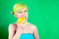 La muchacha hermosa con el pelo verde come el limón en fondo verde Fotografía de archivo libre de regalías