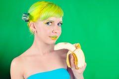 La muchacha hermosa con el pelo verde come el plátano en fondo verde Imágenes de archivo libres de regalías