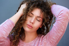 La muchacha hermosa con las manos en pelo y ojos se cerró Imagenes de archivo