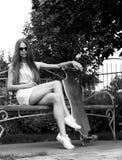 La muchacha hermosa con longboard asiste en banco fotografía de archivo