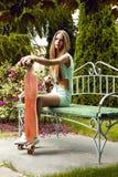 La muchacha hermosa con longboard asiste en banco fotos de archivo libres de regalías