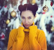 La muchacha hermosa con los ojos azules en un suéter amarillo debajo de un árbol de navidad nevado con la Navidad juega Una mucha Fotos de archivo libres de regalías