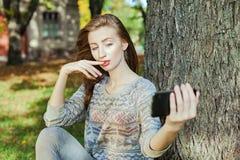 La muchacha hermosa con los ojos azules hace el selfie al aire libre Fotos de archivo libres de regalías