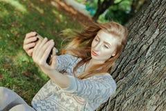 La muchacha hermosa con los ojos azules hace el selfie al aire libre Imagen de archivo libre de regalías