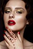 La muchacha hermosa con maquillaje de la tarde, los labios rojos en diamantes artificiales y el diseño manicure clavos Cara de la foto de archivo