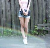 La muchacha hermosa con pantalones cortos de los vidrios y la blusa rosada se coloca delante de una cerca de madera, zapatillas d Imágenes de archivo libres de regalías