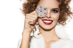 La muchacha hermosa con sonrisa del maquillaje de la tarde toma el copo de nieve cristal Imágenes de archivo libres de regalías