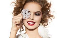 La muchacha hermosa con sonrisa del maquillaje de la tarde toma el copo de nieve cristal Imagenes de archivo