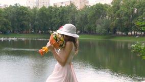 La muchacha hermosa con un ramo de flores gira en danza Cámara lenta almacen de video