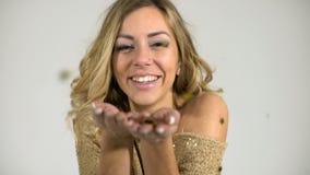 La muchacha hermosa con un suéter del oro lanza confeti en un fondo blanco almacen de video