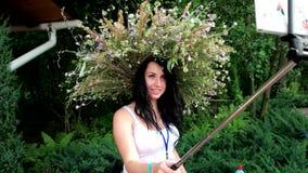 La muchacha hermosa con una guirnalda de flores en su cabeza hace que el selfie al aire libre llama por teléfono para el instagra