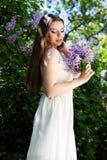 La muchacha hermosa con una lila florece Imagenes de archivo