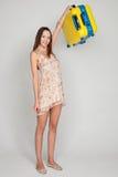 La muchacha hermosa con una maleta del amarillo ama viajar Foto de archivo