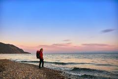 La muchacha hermosa con una mochila camina en la costa en la puesta del sol Imagenes de archivo