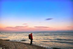 La muchacha hermosa con una mochila camina en la costa en la puesta del sol Foto de archivo libre de regalías