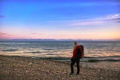 La muchacha hermosa con una mochila camina en la costa en la puesta del sol Fotografía de archivo libre de regalías