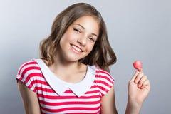 La muchacha hermosa con una piruleta en su mano está presentando en un fondo gris muchacha en un vestido en rojo con las rayas bl Imagen de archivo