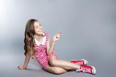 La muchacha hermosa con una piruleta en su mano está presentando en un fondo gris muchacha en un vestido en rojo con las rayas bl Fotografía de archivo libre de regalías