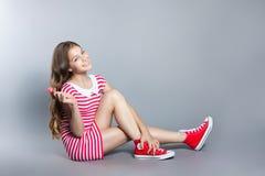 La muchacha hermosa con una piruleta en su mano está presentando en un fondo gris muchacha en un vestido en rojo con las rayas bl Fotos de archivo