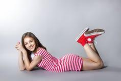 La muchacha hermosa con una piruleta en su mano está presentando en un fondo gris muchacha en un vestido en rojo con las rayas bl Fotografía de archivo