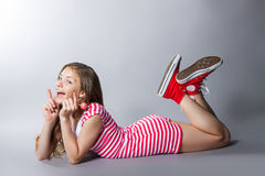 La muchacha hermosa con una piruleta en su mano está presentando en un fondo gris muchacha en un vestido en rojo con las rayas bl Imagenes de archivo