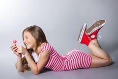 La muchacha hermosa con una piruleta en su mano está presentando en un fondo gris muchacha en un vestido en rojo con las rayas bl Imágenes de archivo libres de regalías