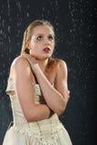 La muchacha hermosa congela en lluvia Imagen de archivo libre de regalías