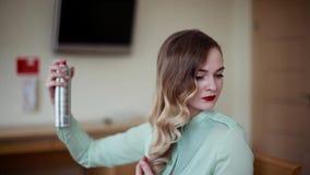 La muchacha hermosa corrige el peinado Laca para el pelo metrajes