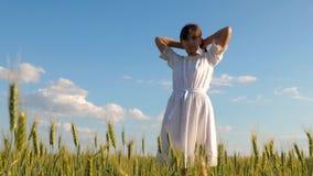 La muchacha hermosa corrige el pelo largo con las manos y las sonrisas en campo con trigo contra el cielo azul Cámara lenta metrajes