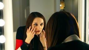 La muchacha hermosa corrige maquillaje delante de un espejo en el cuarto almacen de metraje de vídeo