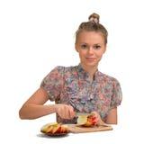 La muchacha hermosa corta las manzanas para la empanada Imagenes de archivo