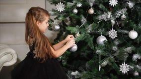 La muchacha hermosa cuelga los juguetes en el árbol de navidad almacen de video
